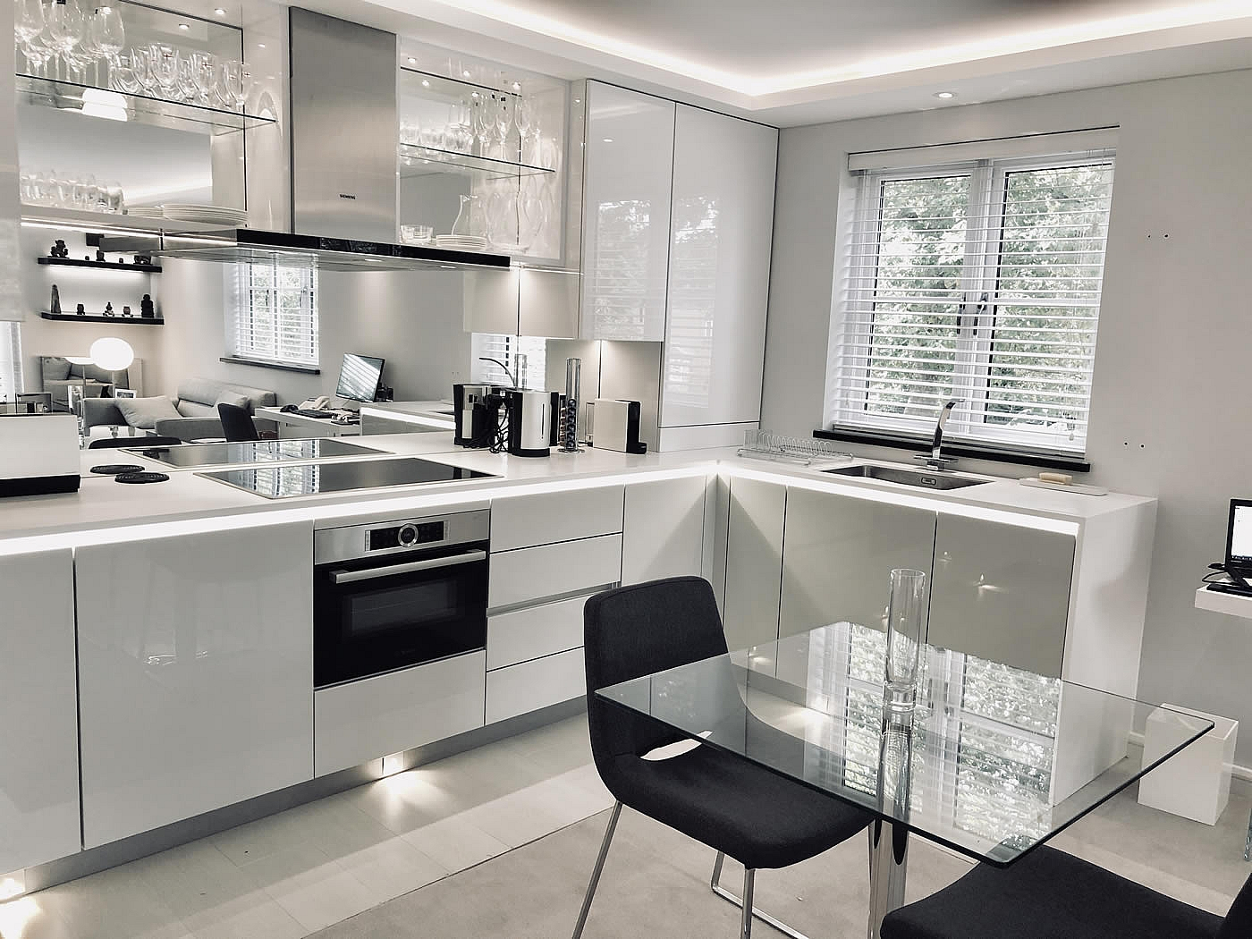 Designer White Kitchen for London pied-a-terre apartment, units are Hacker-Systemat high gloss grey lacquer with the upper units in high gloss white