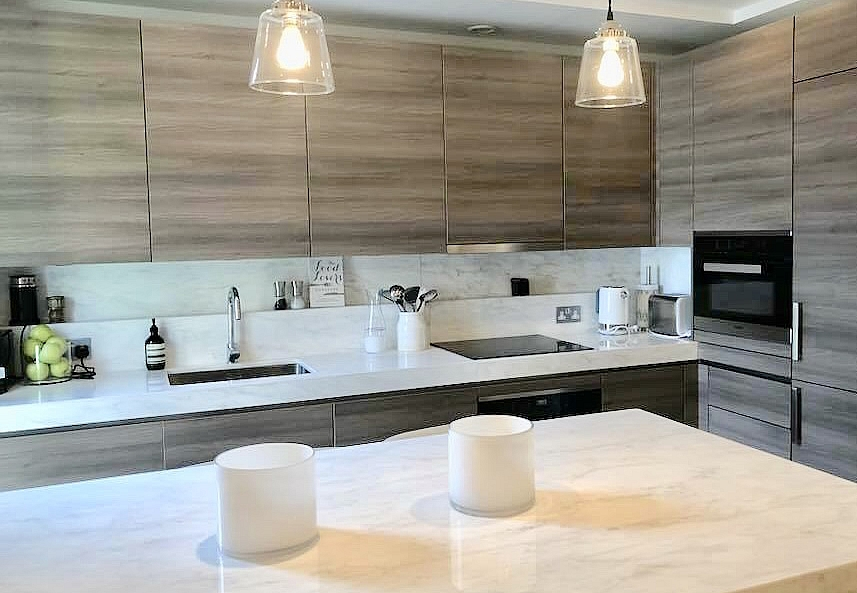 Exclusive designer kitchen marble surfaces South Kensington, with Miele appliances handle-less design in a horizontal veneer cabinets